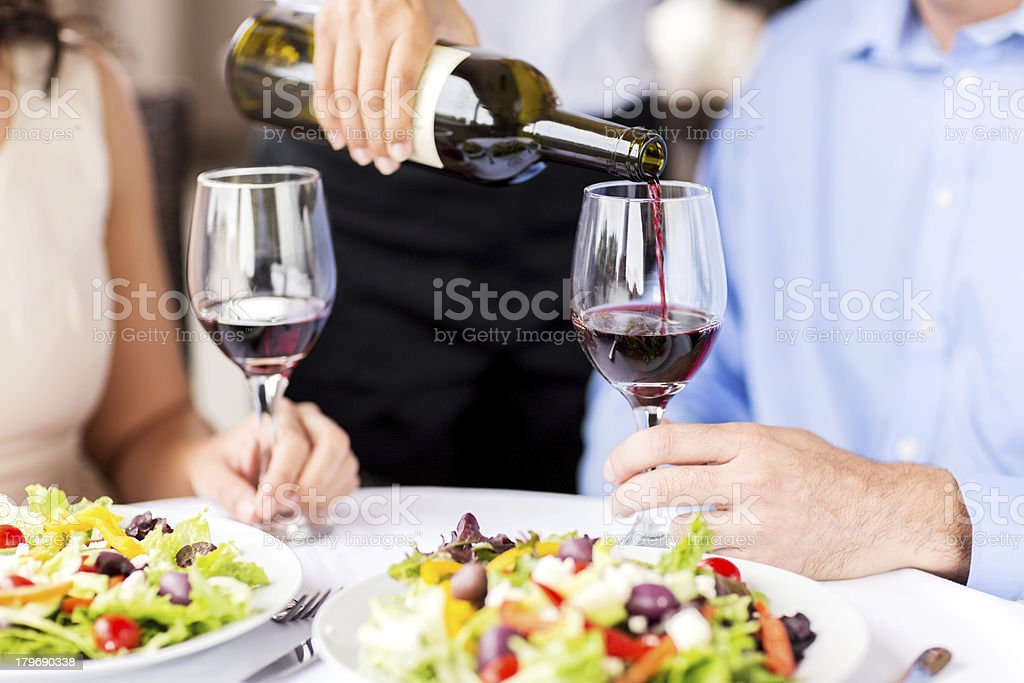 Close-Up Of Waitress Pouring Red Wine For Couple In Restaurant royalty-free stock photo