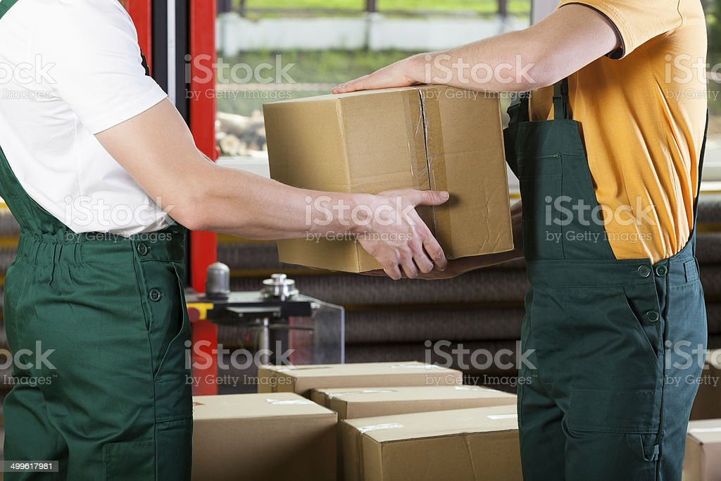 Close-up of warehouse workers with box stock photo