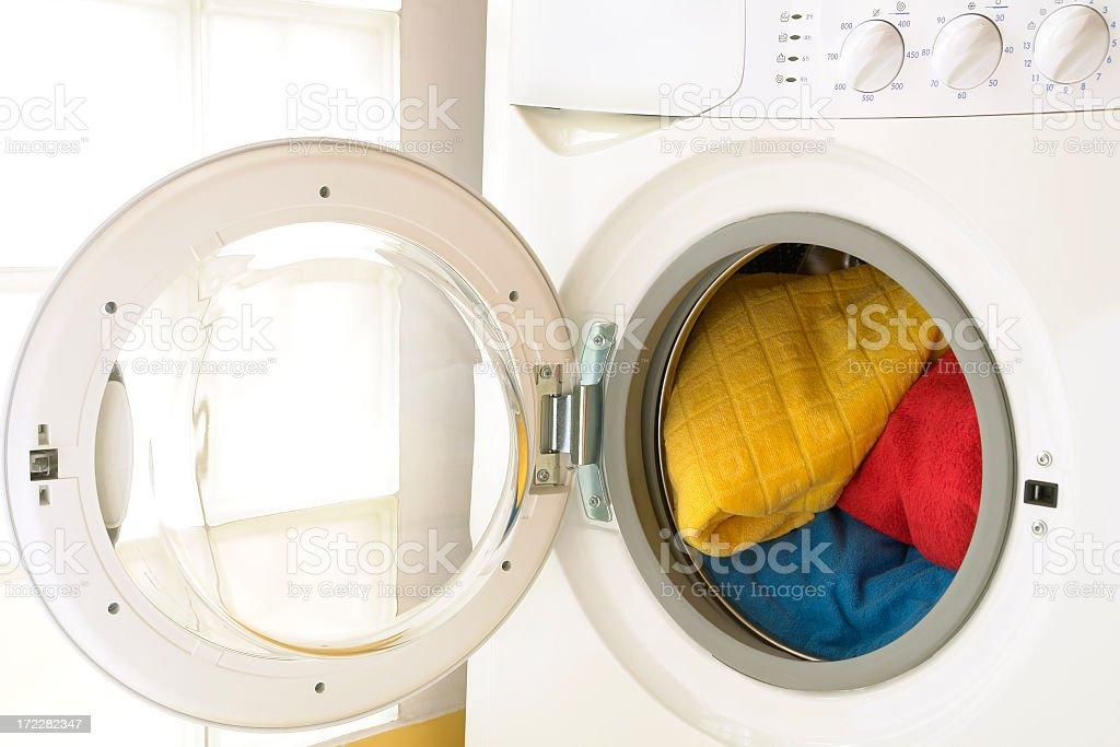 Close-up of washing machine, opened door, laundry inside, three towels royalty-free stock photo