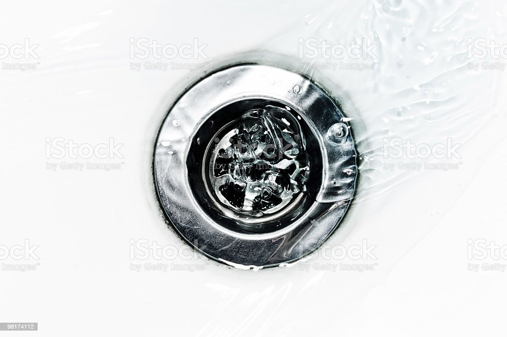 Closeup of Water flowing down a drain stock photo