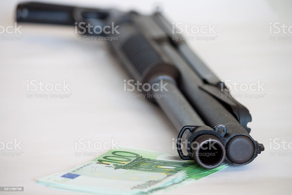 Close-up of weapon lying on heap with hundred dollar stock photo