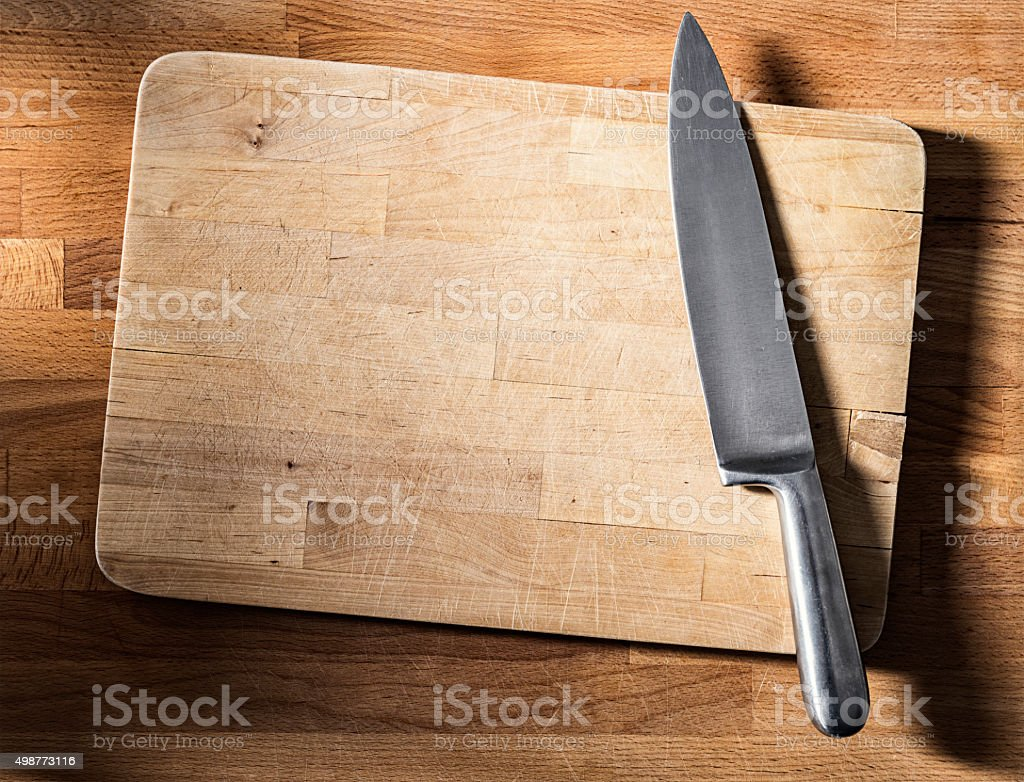 Close-up of weathered wooden cutting board, steel knife, directly above stock photo