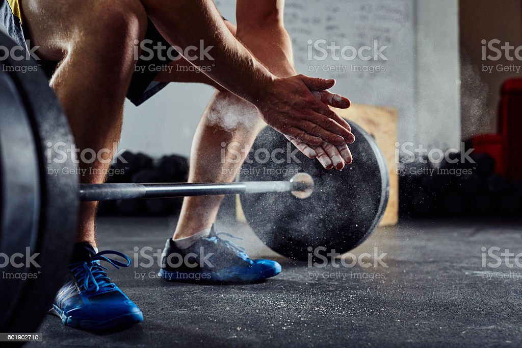 Closeup of weightlifter clapping hands before  barbell workout a stock photo
