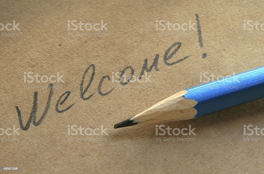 Close-up of welcome written on brown paper, in pencil royalty-free stock photo