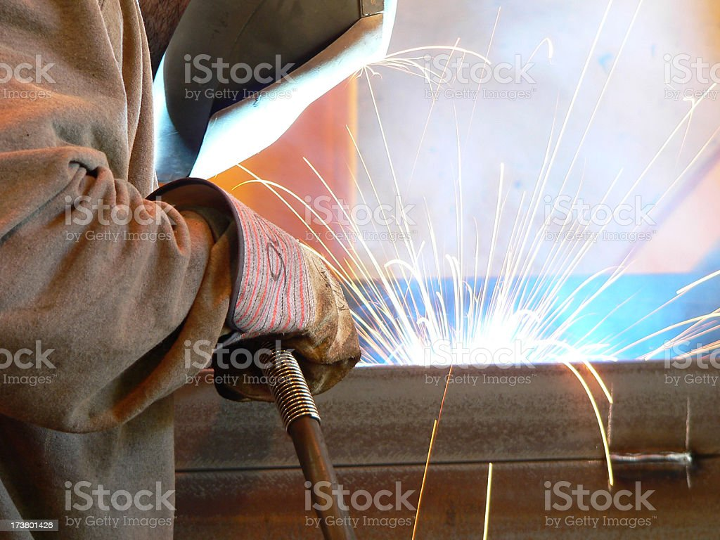 Closeup of welder with dramatic flairs from his tools stock photo