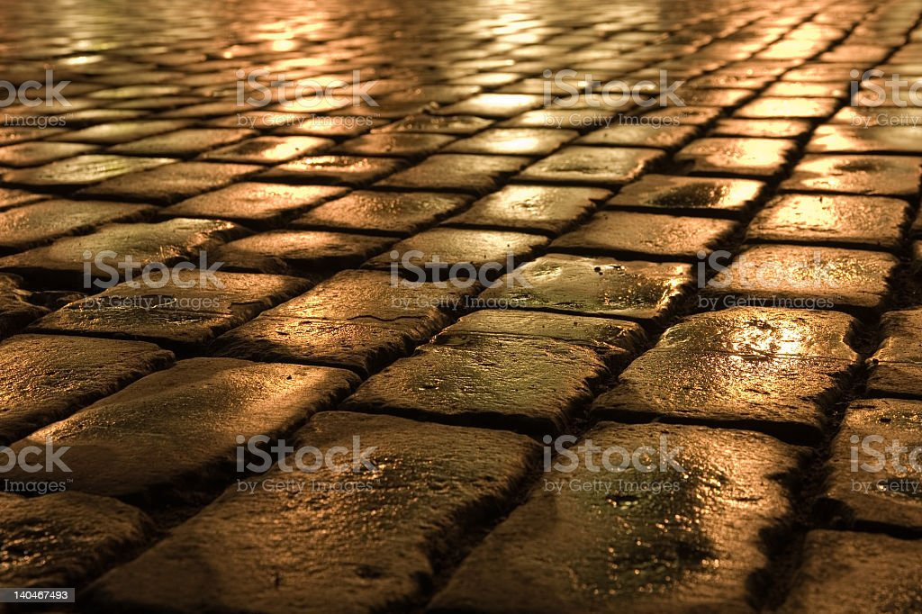 Close-up of wet stone brick road at night stock photo