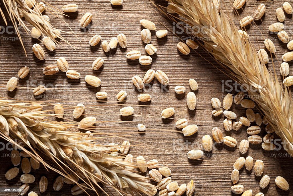 Close-up of wheat scattered on wooden table stock photo