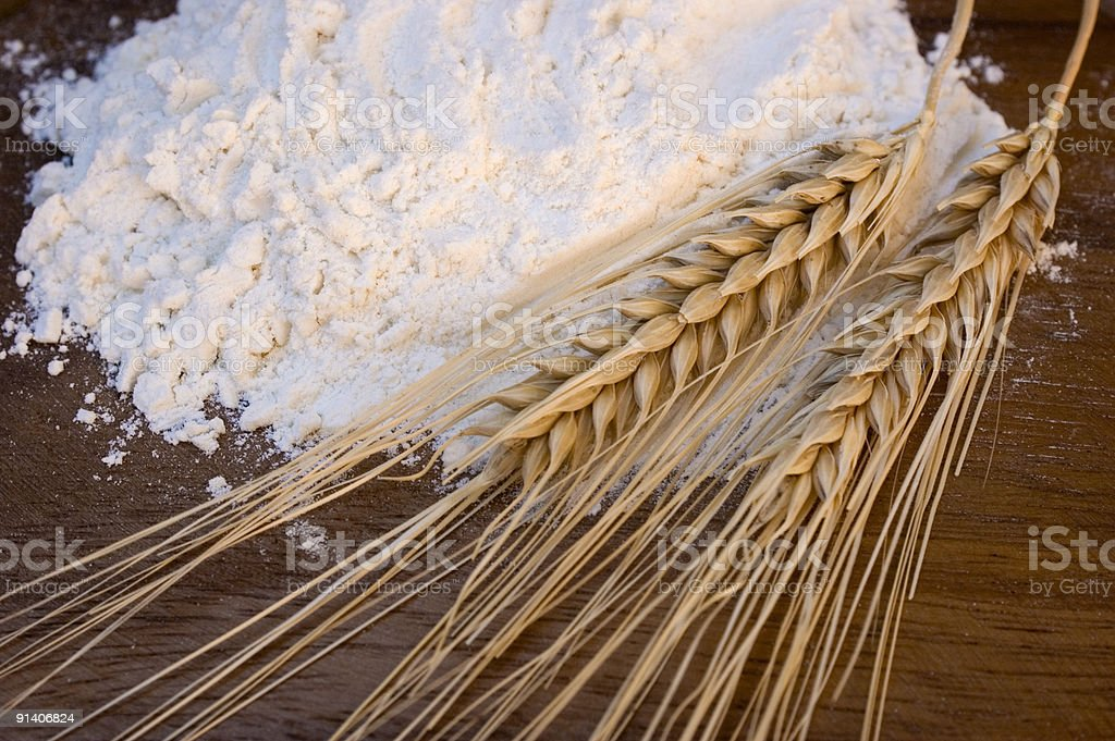 A close-up of wheat stalks and refined flour on wood royalty-free stock photo