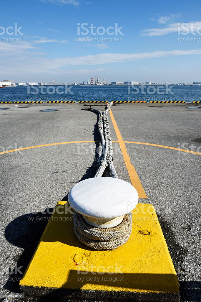 Close-up of white bollard with hawser against Tokyo bay area stock photo