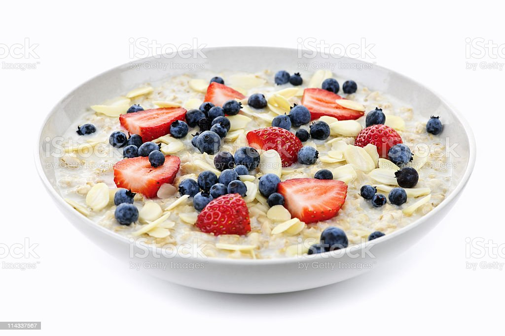 Close-up of white bowl of oatmeal with berries against white royalty-free stock photo