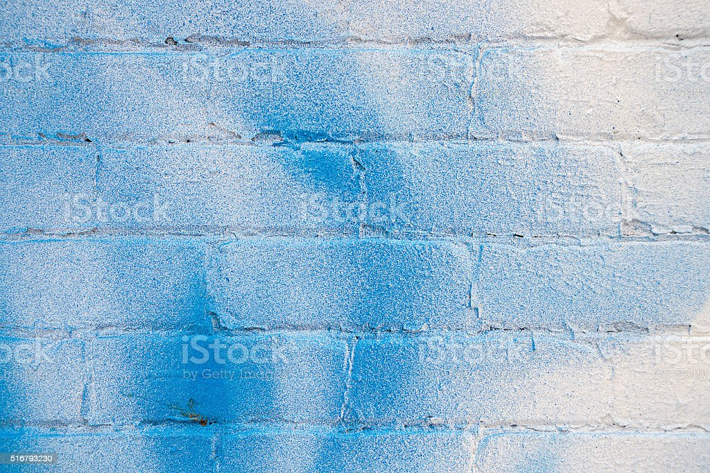 Closeup of white brick wall with blue spray stains stock photo