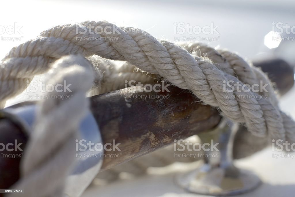 Closeup of white fiber rope wrapped around wooden pole stock photo