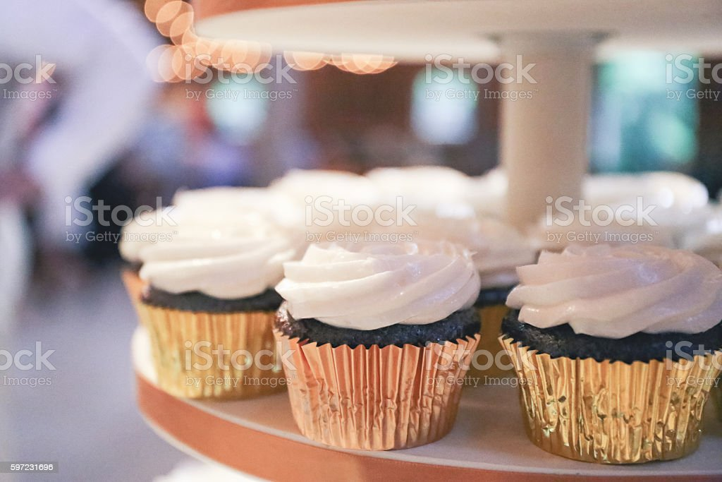 Closeup of White Frosted Cupcakes Displayed on Tiered Cake Stand stock photo