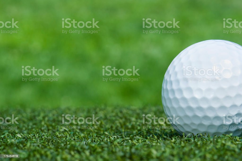 Close-up of white golf ball on the green stock photo
