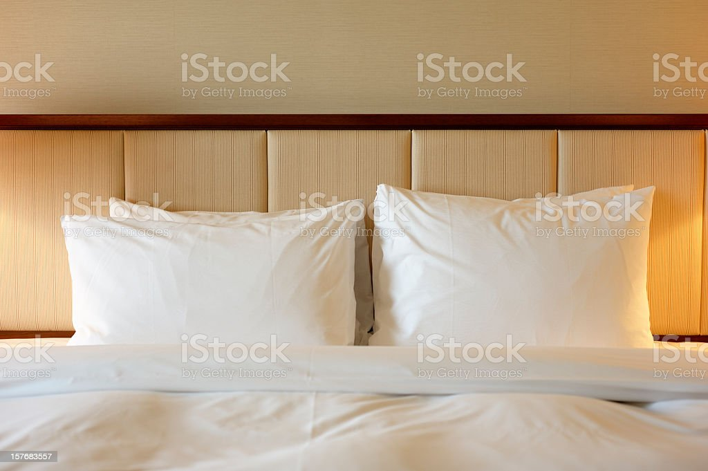 Close-up of white linens over a luxury hotel bed stock photo