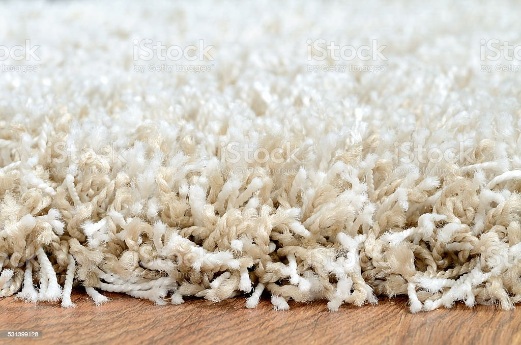 Close-up of white shaggy carpet on brown wooden floor stock photo