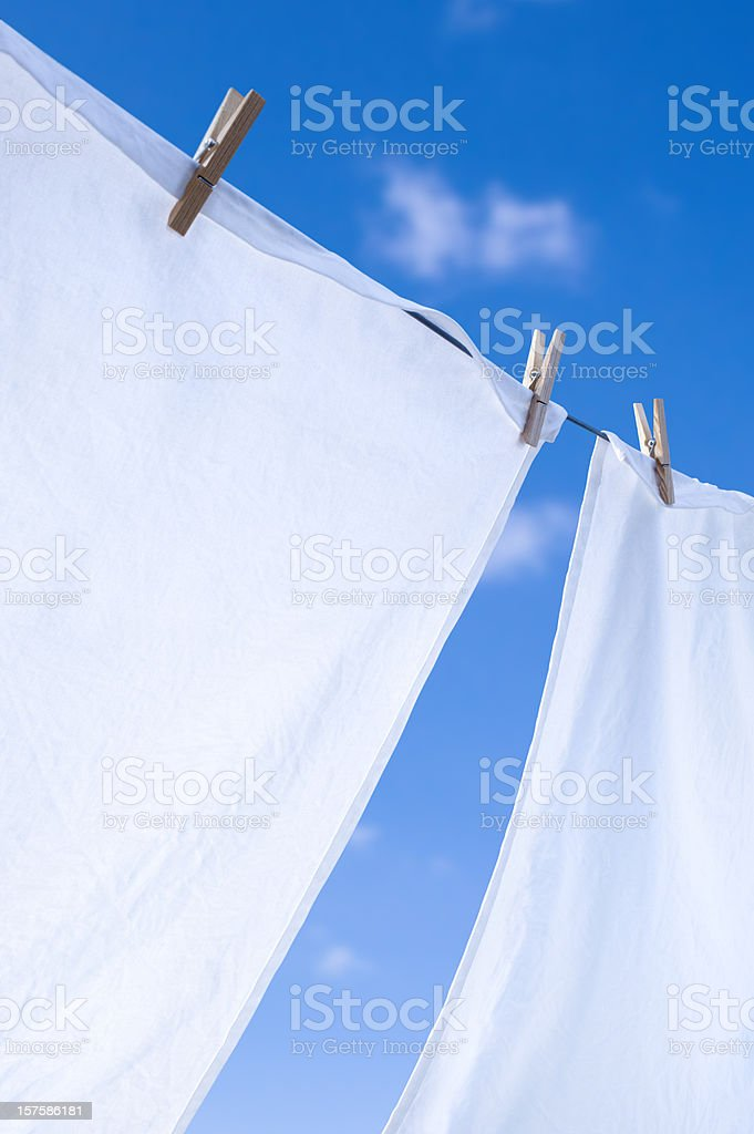Closeup of whites on clothesline under blue sky stock photo