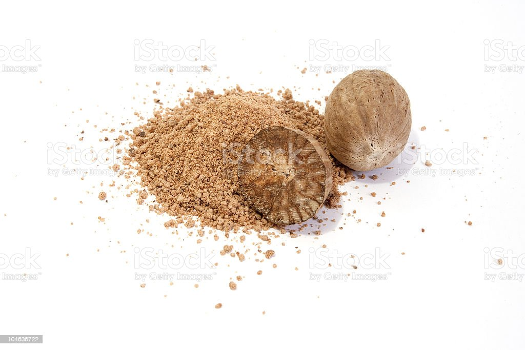 A close-up of whole nutmeg and crushed nutmeg stock photo