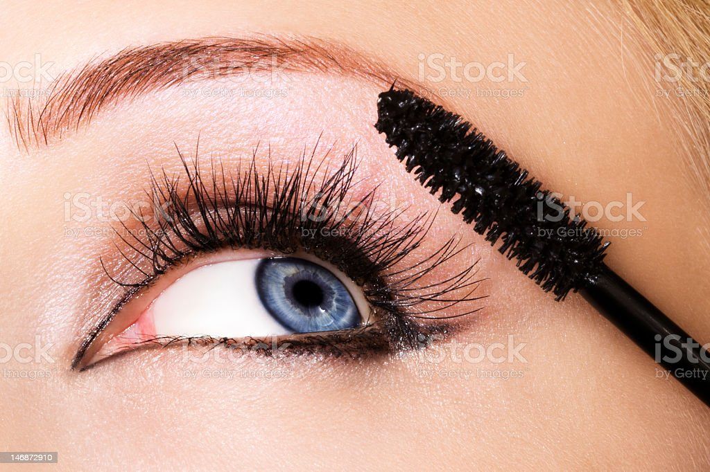 Close-up of woman applying mascara to her eye stock photo
