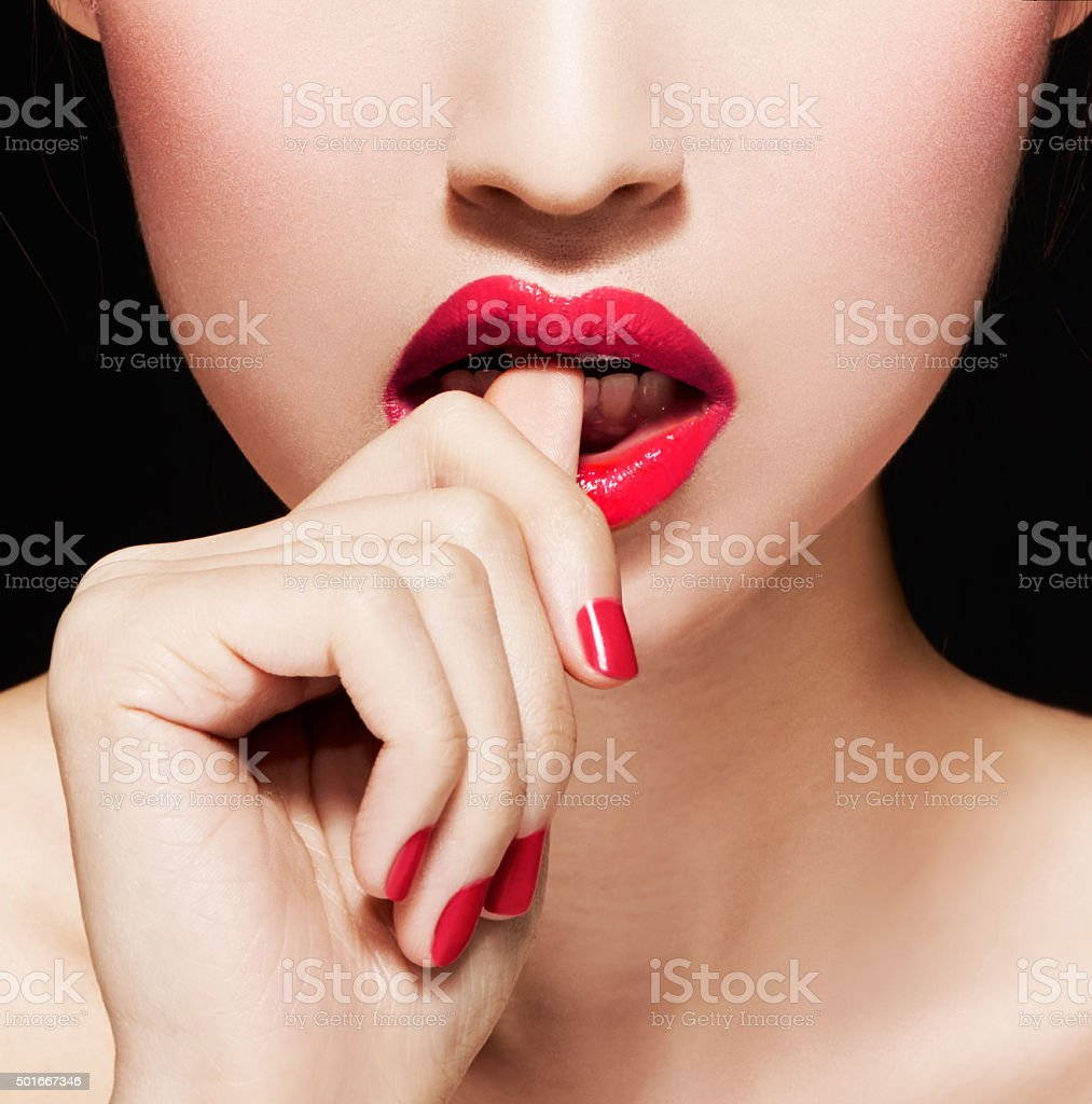 Closeup of woman biting nails or fingers.Red lips and manicure. stock photo