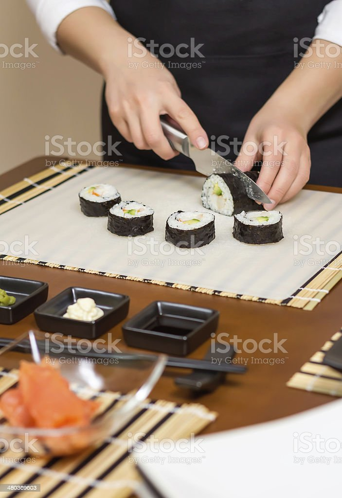 Closeup of woman chef cutting japanese sushi roll stock photo