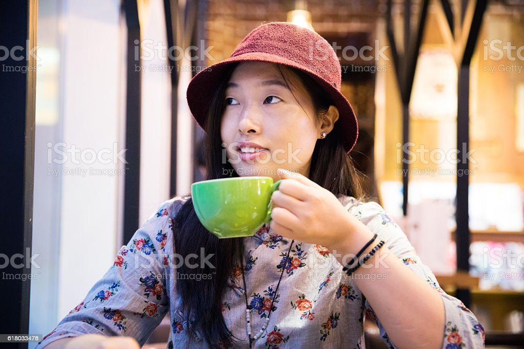close-up of woman drinking coffee, focus on hand and cup stock photo