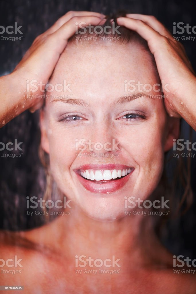 Closeup of woman enjoying a shower against dark background royalty-free stock photo