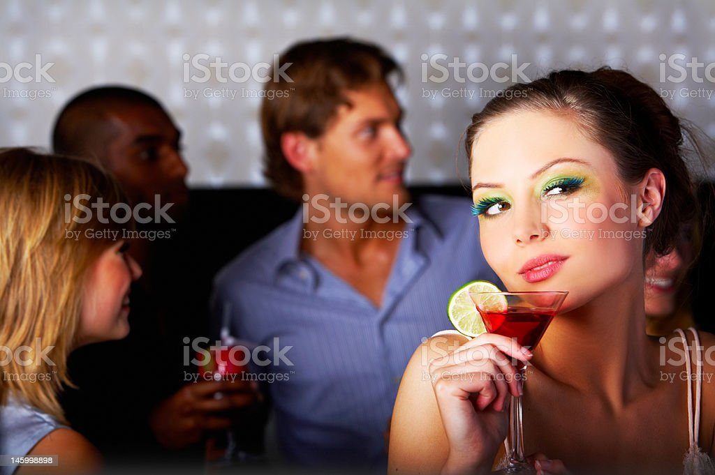 Close-up of woman enjoying drink with her friends in disco royalty-free stock photo