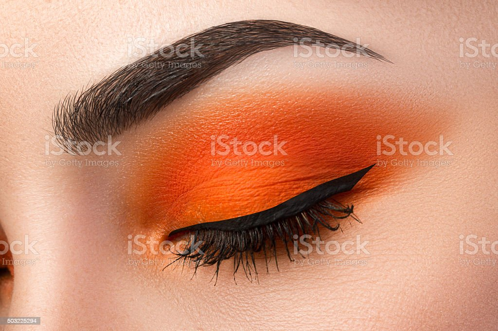Close-up of woman eye with beautiful orange smokey eyes stock photo