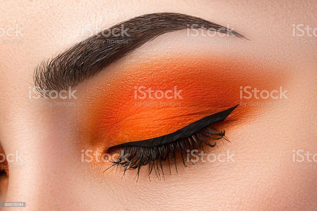 Close-up of woman eye with beautiful orange smokey eyes stock photo