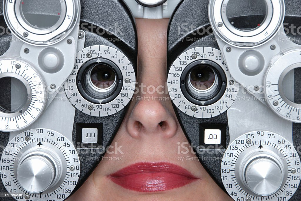 Close-up of woman face as she peers through phoropter royalty-free stock photo