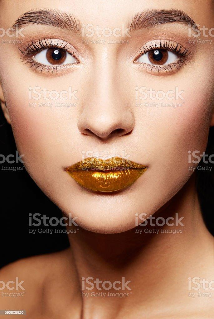 Closeup of woman face.perfect skin, gold lips,long eyelashes. stock photo
