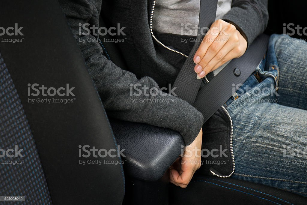 Closeup of woman fastening seat belt in car stock photo
