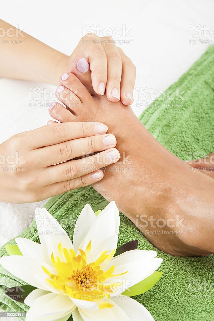 Close-up of woman Feet Undergoing Massage near to one flower stock photo