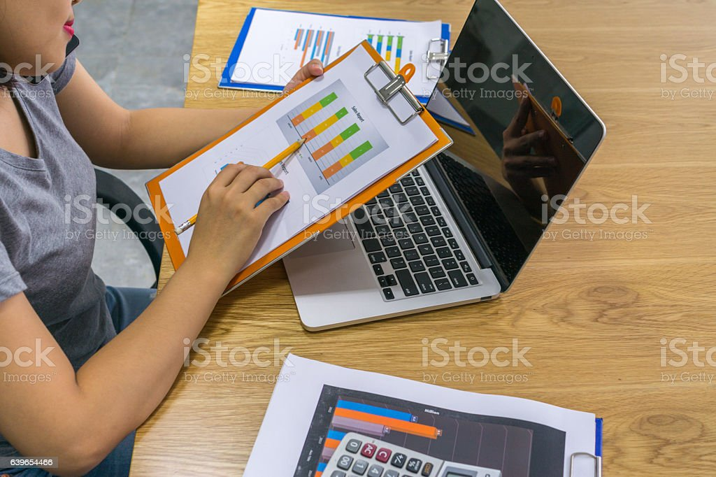 Close-up of woman hand holding pencil pointing at sales report stock photo