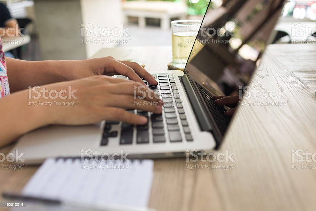 Close-up of woman hand typing on laptop stock photo