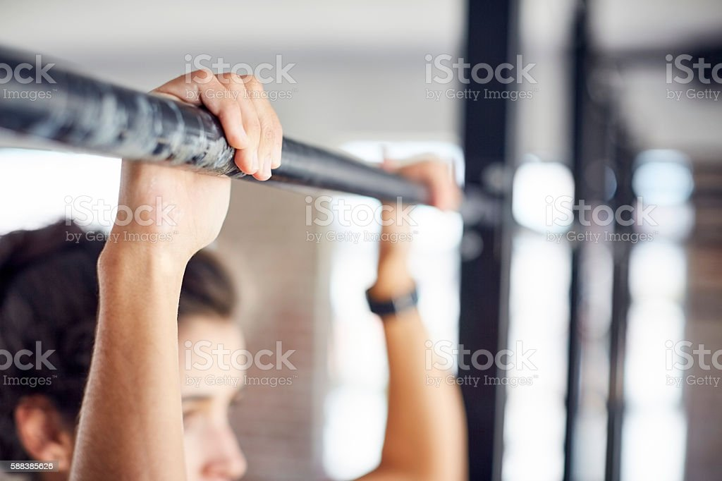 Close-up of woman hands exercising on pull-up bar at gym stock photo
