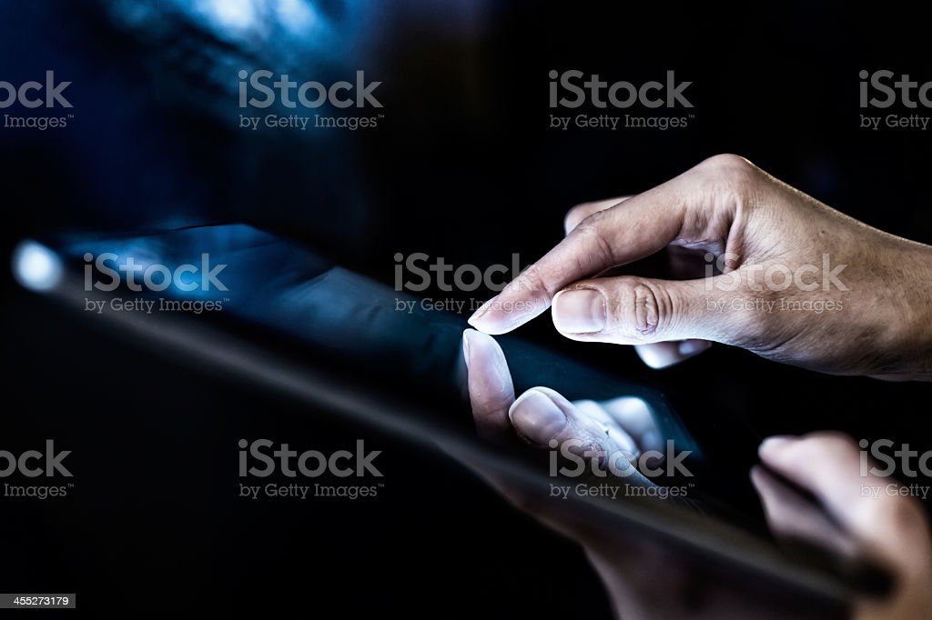 Closeup of woman holding a digital tablet in the dark stock photo