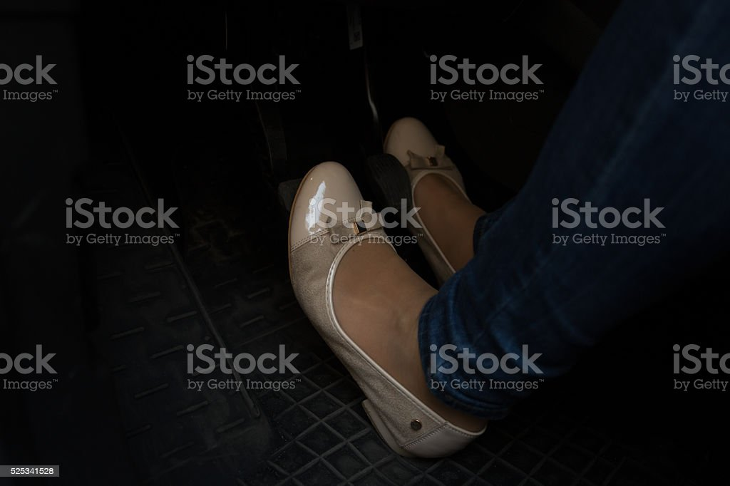 Closeup of woman in comfortable shoes pressing car pedals stock photo