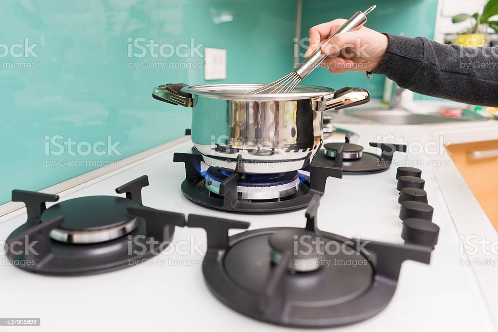 closeup of woman  in kitchen  cooking soup on a stove stock photo