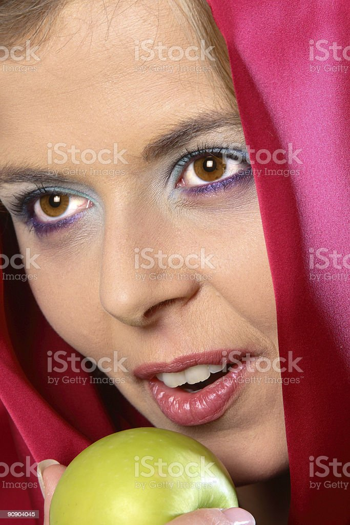 Closeup of woman in red scarf with apple royalty-free stock photo
