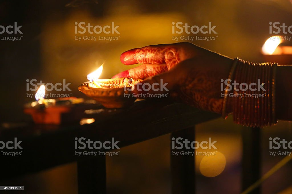 Close-up of woman lighting diya on railing stock photo