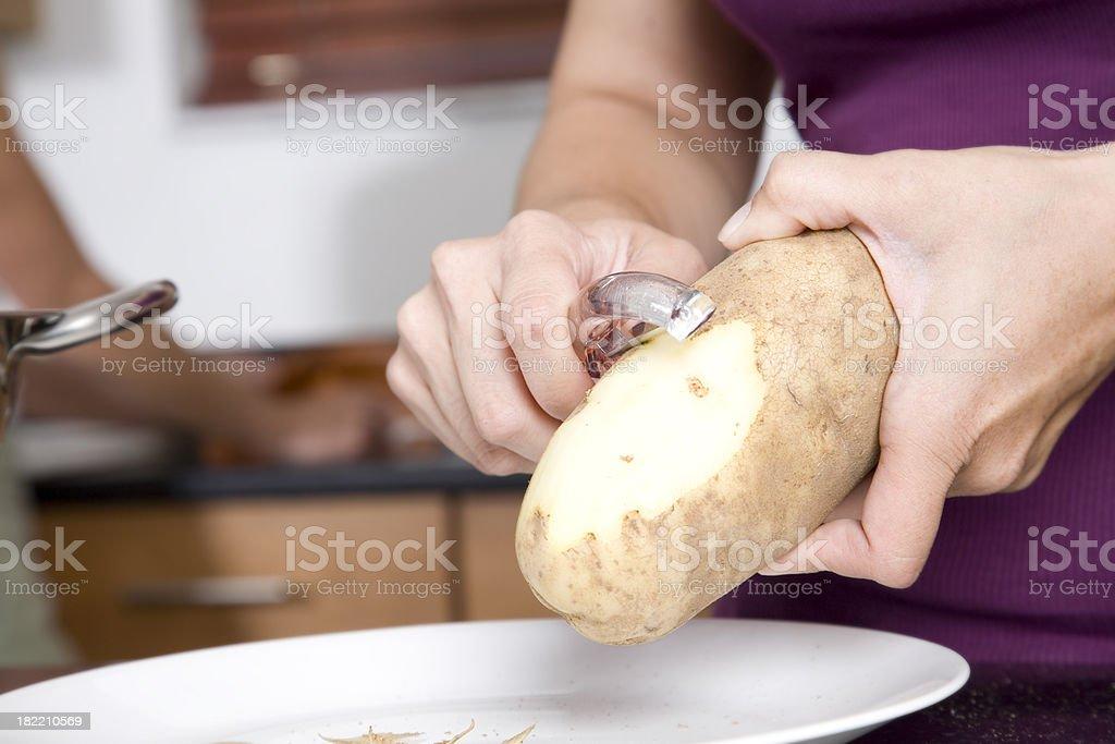 Closeup of Woman Peeling a potato stock photo