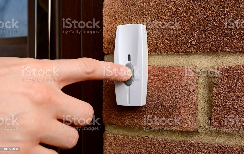 Close-up of woman pressing a doorbell stock photo
