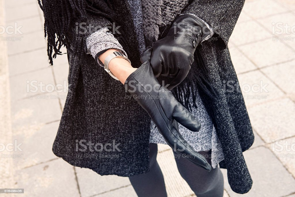close-up of woman putting on her gloves stock photo
