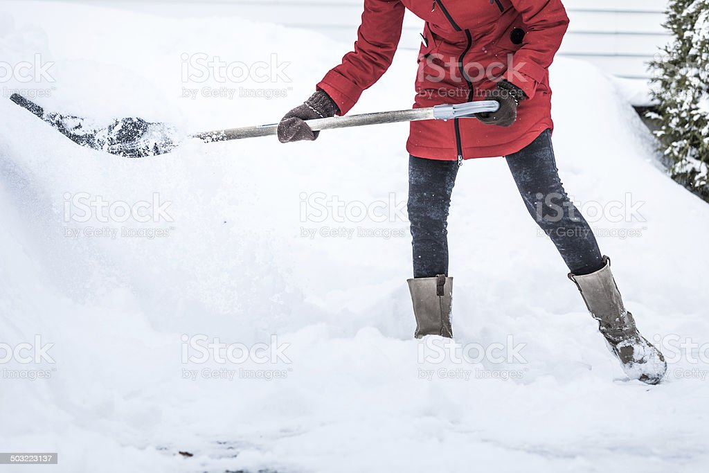 Close-up of Woman Shoveling her Parking lot stock photo