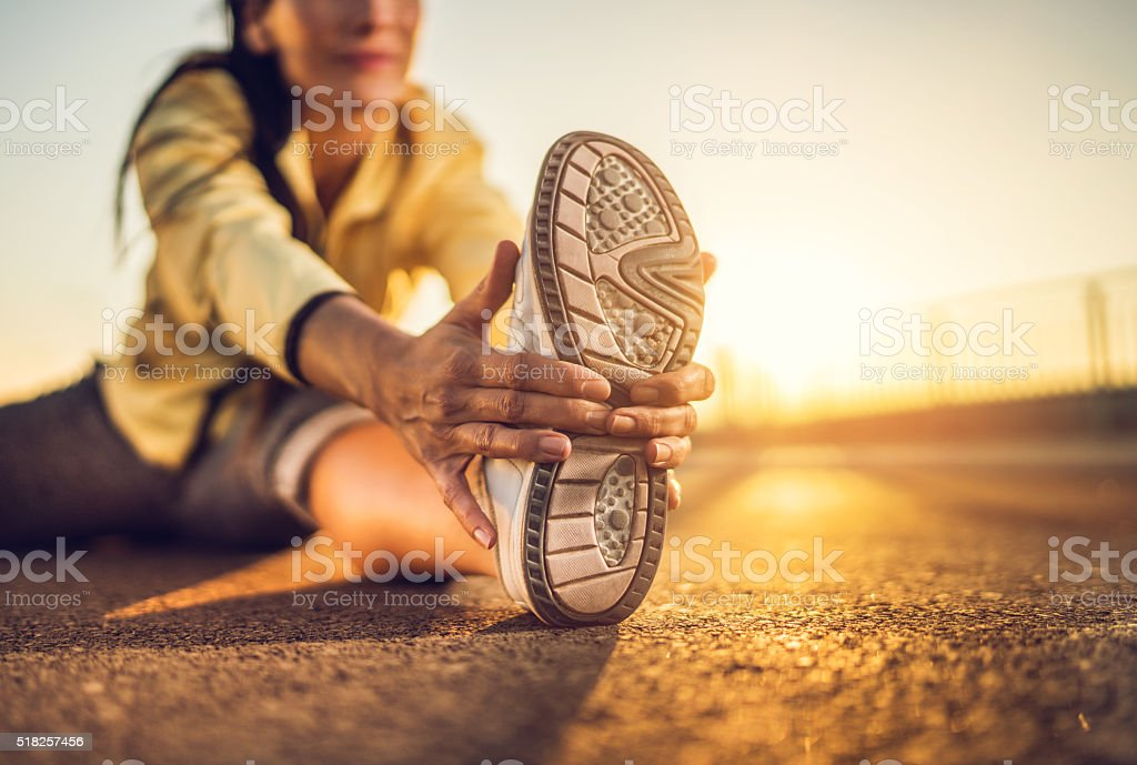 Close-up of woman stretching her leg at sunset. stock photo