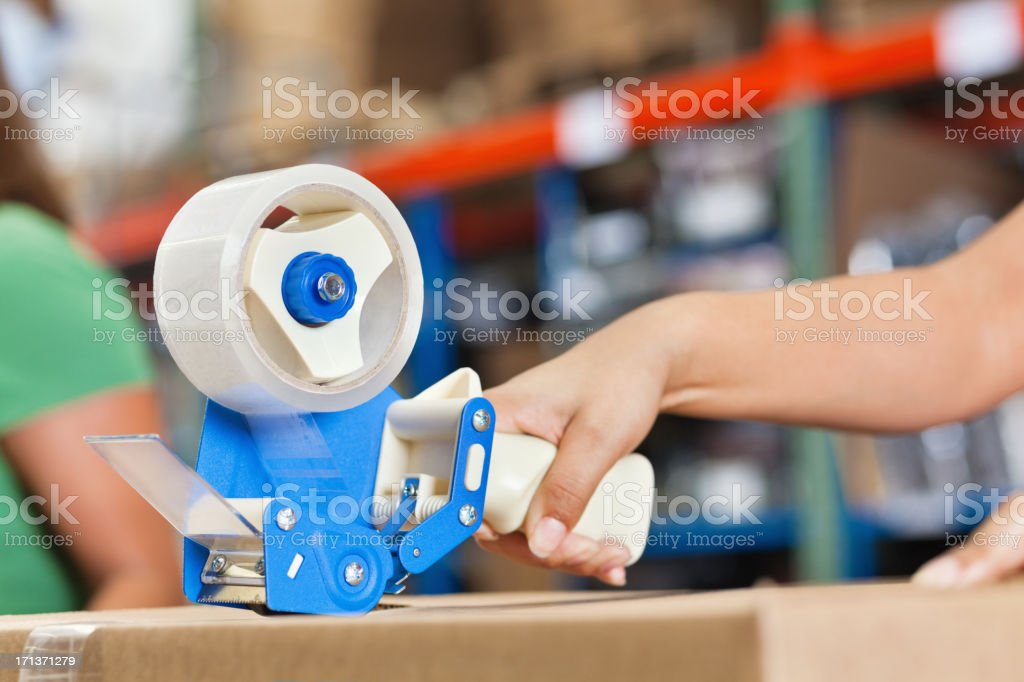 Closeup of woman taping box in warehouse packing distribution center stock photo