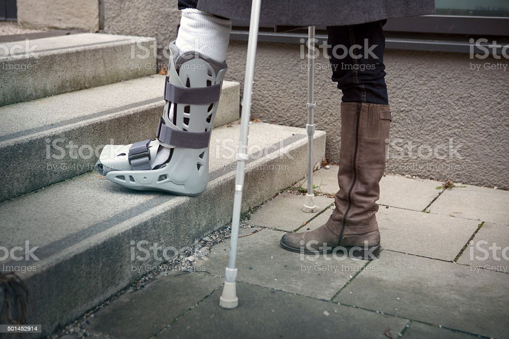 closeup of woman walking with crutches stock photo