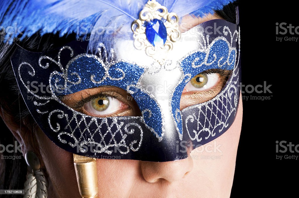 Closeup of woman with green eyes and blue mask. stock photo